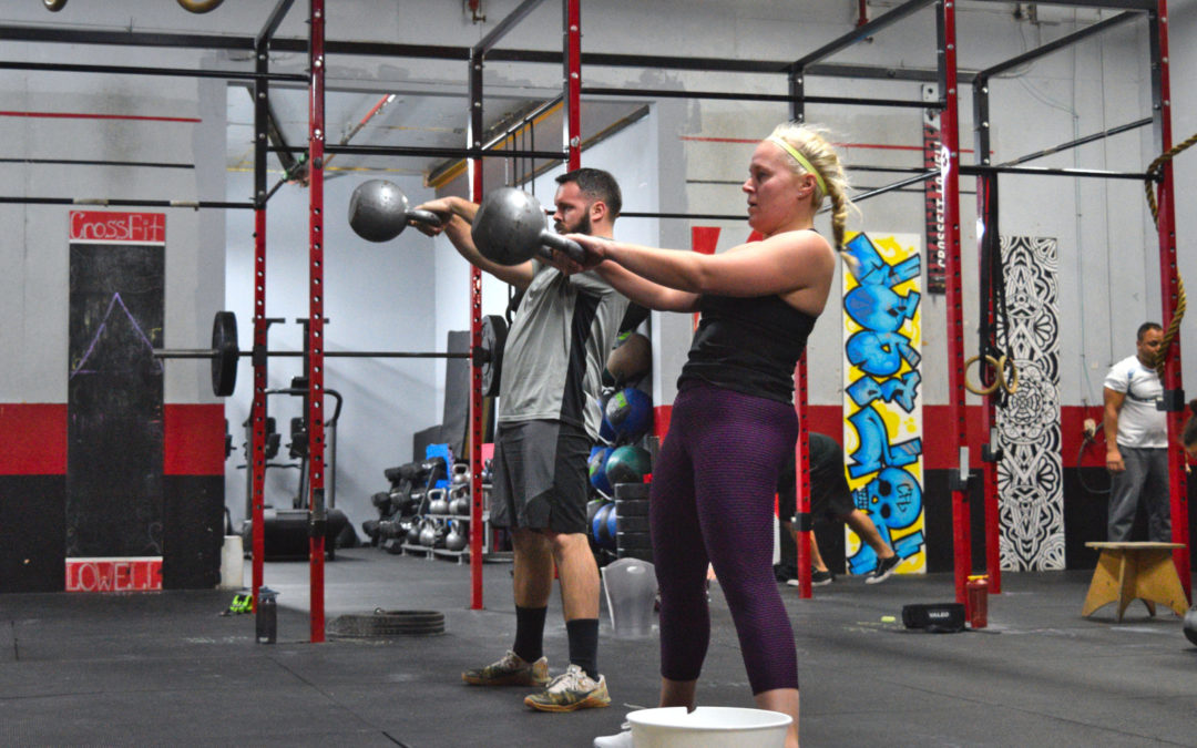 athletes swinging kettlebells
